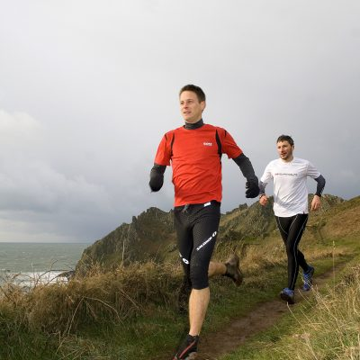 Shane Ohly and James Heraty posing for photos for an articale in the Trail Running Magazine.  Photographed at a very wet, cold and windy Prawle Point in South Devon.